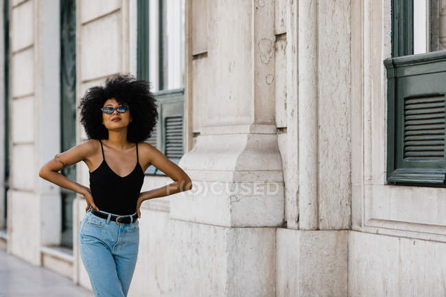 Joven mujer étnica en jeans y camiseta sin mangas caminando y sonriendo a la cámara al aire libre - foto de stock