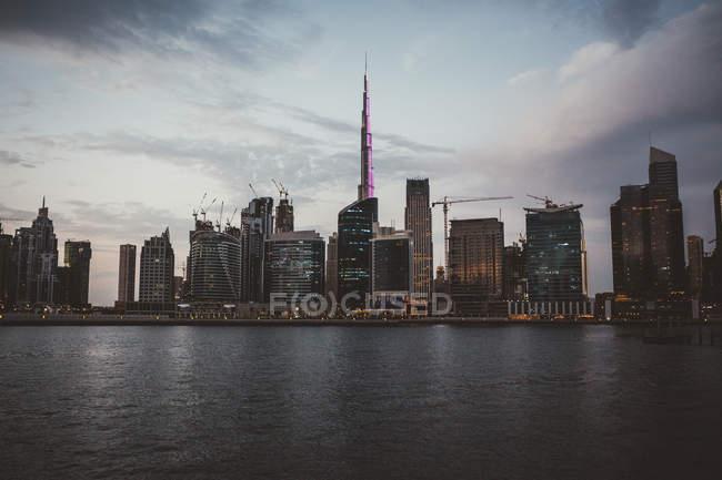Міський пейзаж Дубая з величними освітленою хмарочосами над затокою води в сутінках — стокове фото