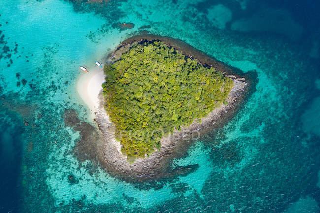 Vue aérienne des bateaux à côté de la petite île tropicale verte parmi l'eau azur de l'océan — Photo de stock