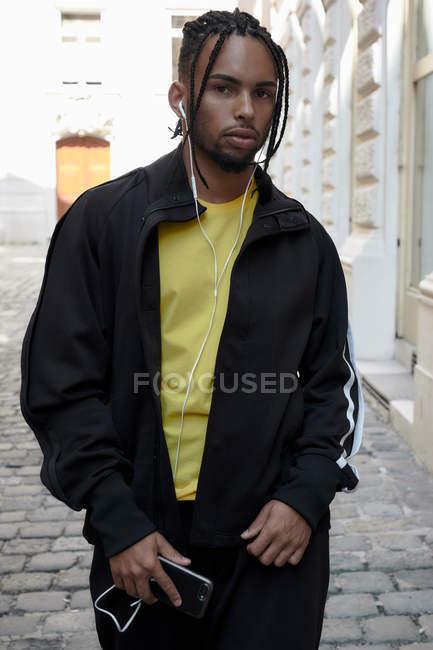Серьезный молодой человек с косичками, наушниками и мобильным телефоном стоит и смотрит в камеру на городском фоне — стоковое фото