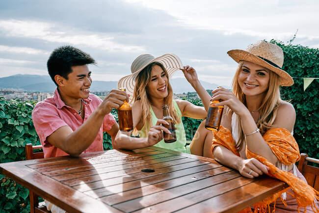 Дві жінки з капелюхами, латина і росіянка, святкують з азійським чоловіком. — стокове фото