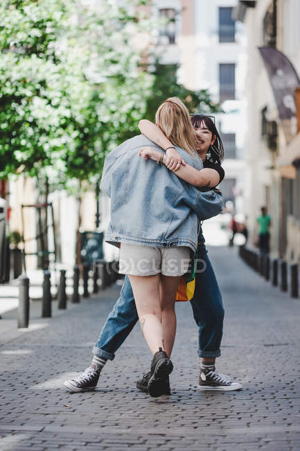 Side view of cheerful young woman hugging and lifting smiling girlfriend while standing on pavement on blurred background of city street — Stock Photo