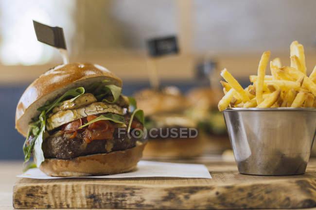Сочный вкусный бургер и жареная картошка на деревянной доске — стоковое фото