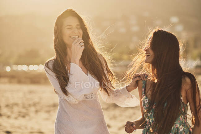 Cheerful adult brunette women in summer light dresses on sandy beach at the golden hour — стоковое фото