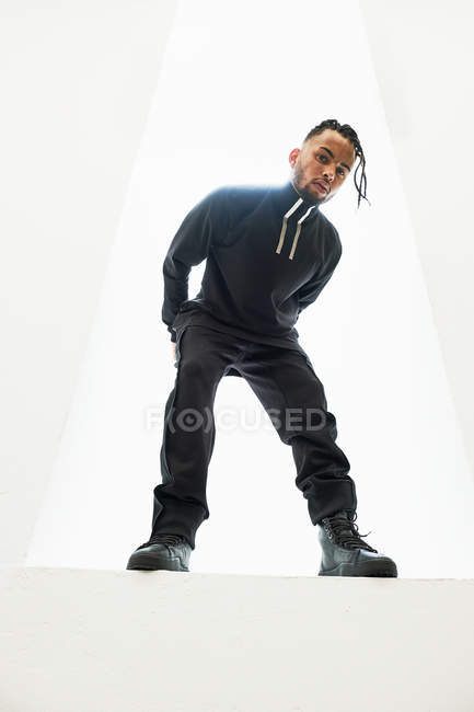 African American man in black clothes with braided hair posing on white background — Stock Photo