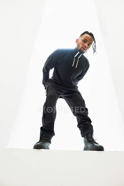 Афроамериканец в черной одежде с плетеными волосами позирует на белом фоне — стоковое фото