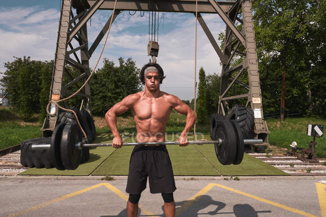 Young bodybuilder with barbell in outdoor gym — Stock Photo