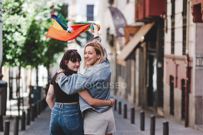Back view of happy lesbians hugging and waving LGBT flag while walking on blurred background of city street — Stock Photo