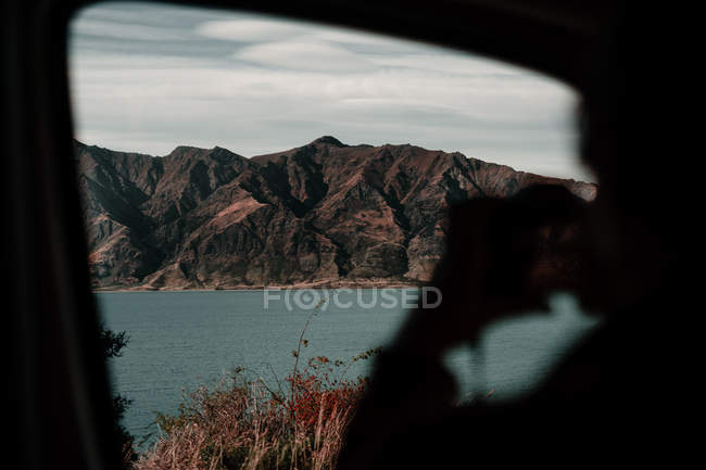 Silhueta da pessoa que toma a foto da paisagem impressionante da montanha do carro no lago Wanaka e no lago Hawea em Nova Zelândia — Fotografia de Stock