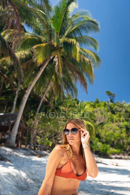 Young woman in swimming suit sunbathing in sandy seashore on background on tropical palms and blue sky — Stock Photo