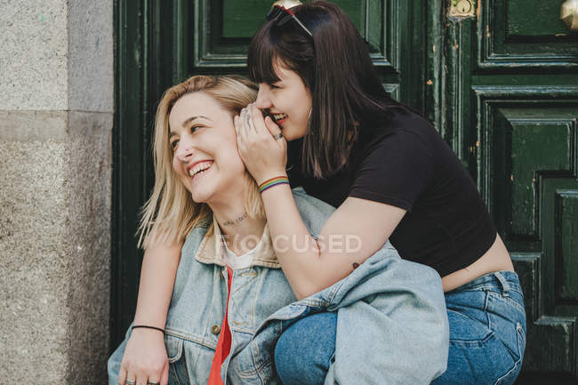 Young woman embracing and telling secret to girlfriend laughing while sitting near entrance of building on city street — Stock Photo
