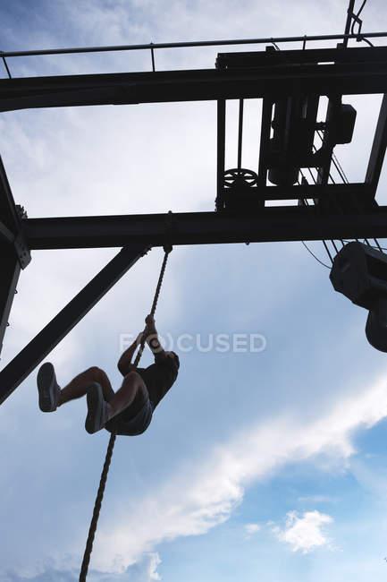 Par-dessous une corde d'escalade méconnaissable pendant un exercice dans un gymnase extérieur — Photo de stock