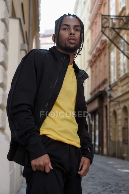 Giovane uomo etnico con i capelli intrecciati indossa tuta sportiva nera guardando la fotocamera su sfondo urbano — Foto stock