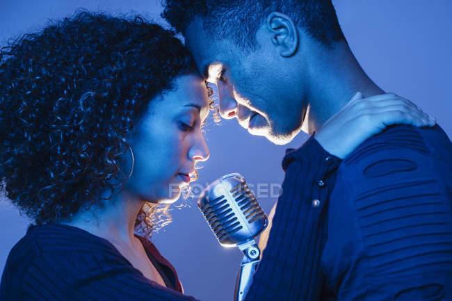 Ласковая молодая африканская пара держит винтажный микрофон и обнимается в синем свете — стоковое фото