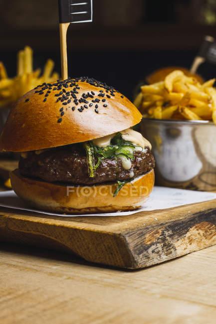 Сочный вкусный бургер и жареная картошка на деревянном столе — стоковое фото