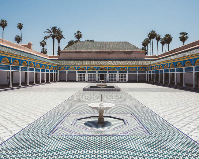 Patio with colorful tiled floor and fountains surrounded with covered gallery and pillars in oriental style, Morocco — Stock Photo