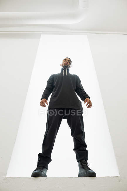 Confident African American man in black clothes with braided hair standing isolated on white background — Stock Photo