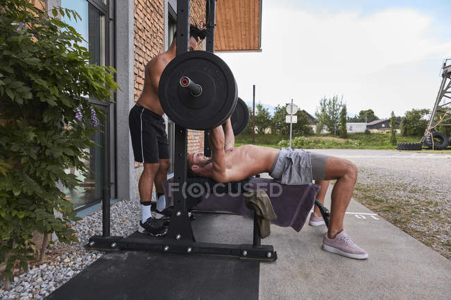 Young guy lifting barbell on street with help of trainer — Stock Photo