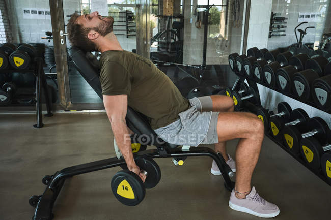 Strong man exercising with dumbbells in gym — Stock Photo