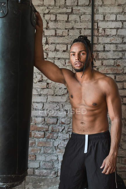 Shirtless African American guy in shorts leaning on boxing bag and looking in camera during workout in gym — Stock Photo