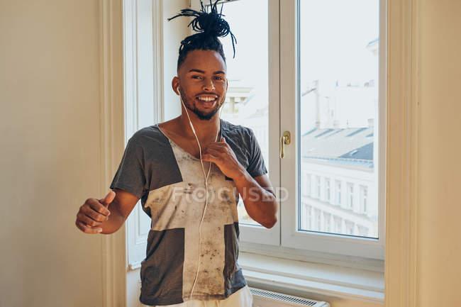 Sorrindo afro-americano homem com tranças dançando à música com fones de ouvido em casa no fundo da janela — Fotografia de Stock