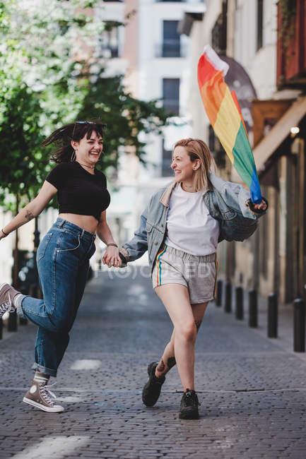 Lesbiennes gaies tenant la main et agitant le drapeau LGBT tout en marchant sur fond flou de la rue de la ville — Photo de stock