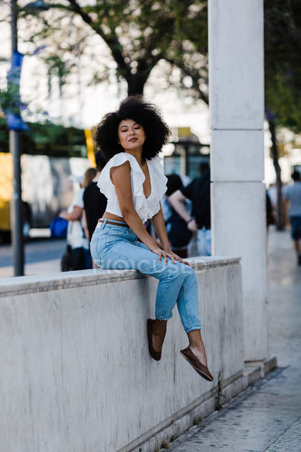 Приваблива етнічна жінка в джинсах і безрукавка відпочиваючи на кам'яних перил проти міського фону — стокове фото