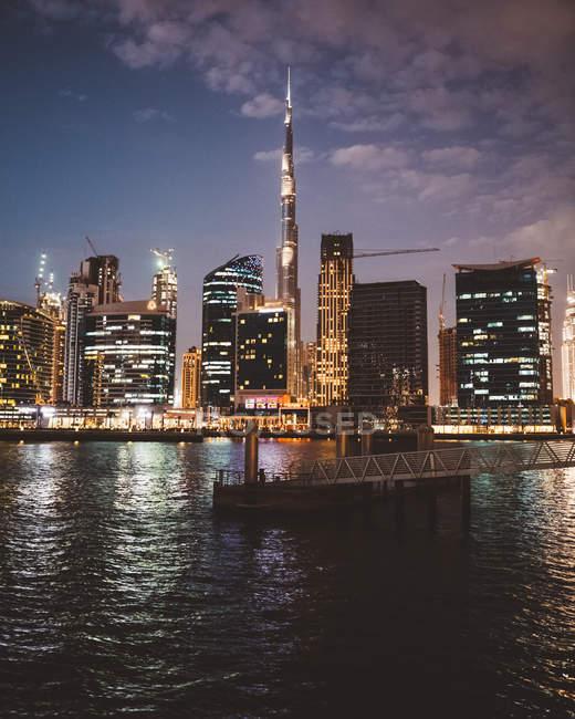 Terraplén contra los resplandecientes rascacielos de la ciudad de Dubái por la noche - foto de stock