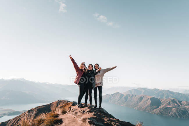 Smiling group of three women in coat standing on high peak of mountains in range smiling stretching arms and looking at camera — Stock Photo