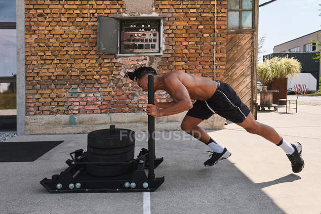 Black guy pulling weights in outdoor gym — Stock Photo