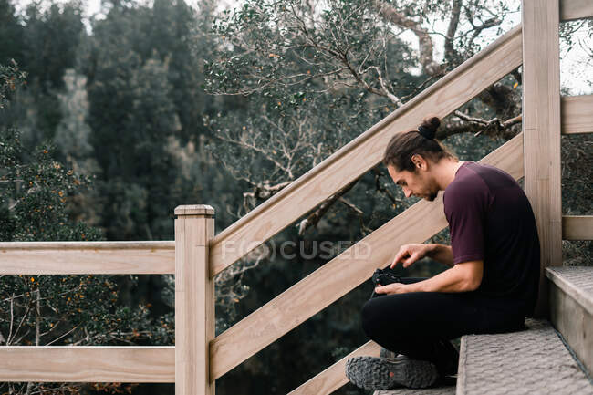Man with camera on wooden stairs — Photo de stock