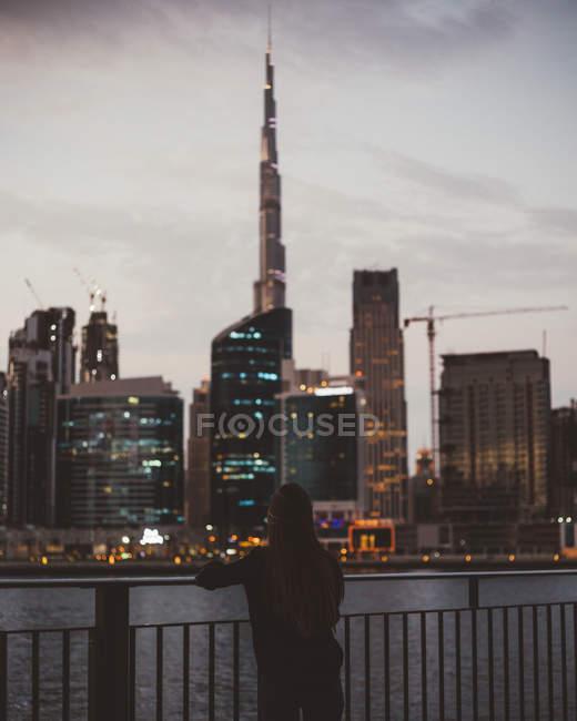 Vista trasera de la persona de pie en el terraplén contra los resplandecientes rascacielos de la ciudad de Dubái - foto de stock