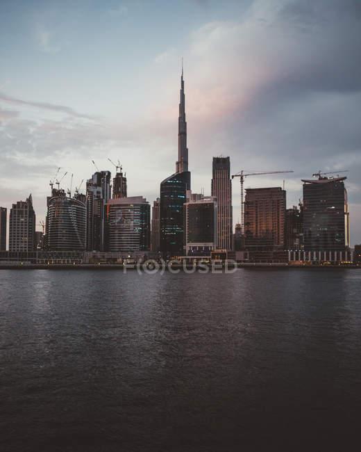 Paisaje urbano de Dubái con majestuosos rascacielos iluminados sobre el agua de la bahía al atardecer - foto de stock