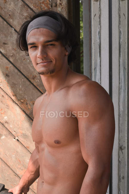 Muscular man posing in front of wooden wall — Fotografia de Stock