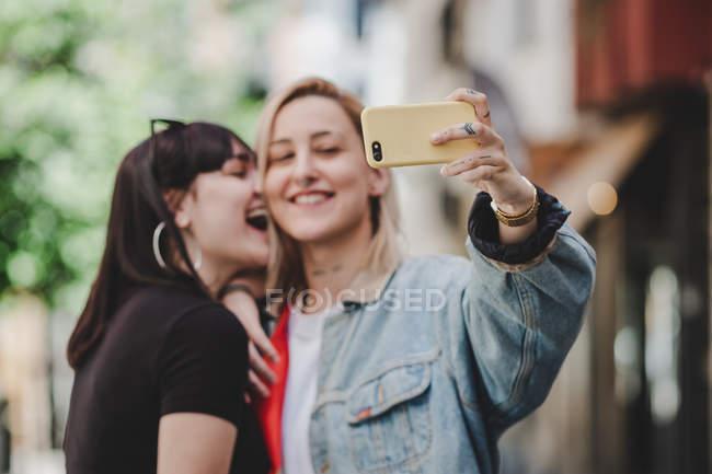 Joyeux jeunes lesbiennes souriantes et posant pour selfie tout en se tenant dans la rue de la ville — Photo de stock