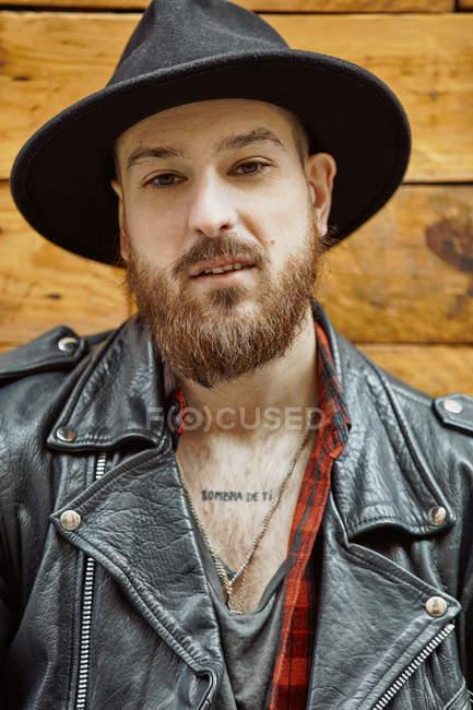 Guapo hombre con gorra chequera y camisa de cuero sonriendo y mirando a lo largo de pie apoyándose en la pared de madera. - foto de stock