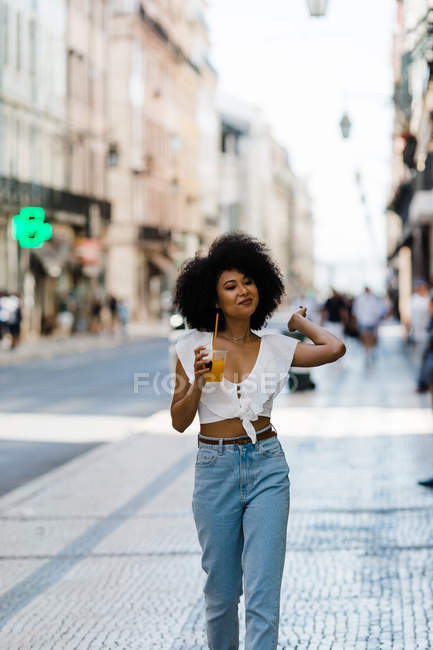 Cheerful trendy African American woman drinking orange juice and looking away on urban background — Stock Photo