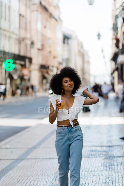 Fröhliche trendige afrikanisch-amerikanische Frau, die Orangensaft trinkt und vor städtischem Hintergrund wegsieht — Stockfoto