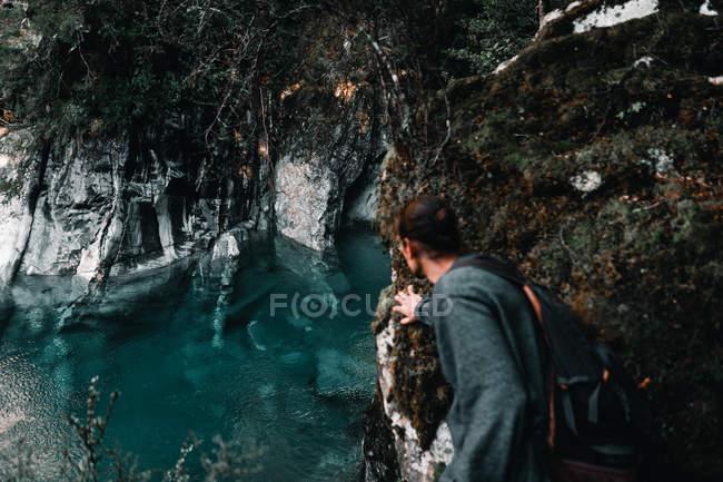 Opinião traseira o homem novo com a trouxa que descobre a água escura de tirar o fôlego da turquesa entre penhascos rochosos cinzentos no lago Wanaka e no lago Hawea Nova Zelândia — Fotografia de Stock