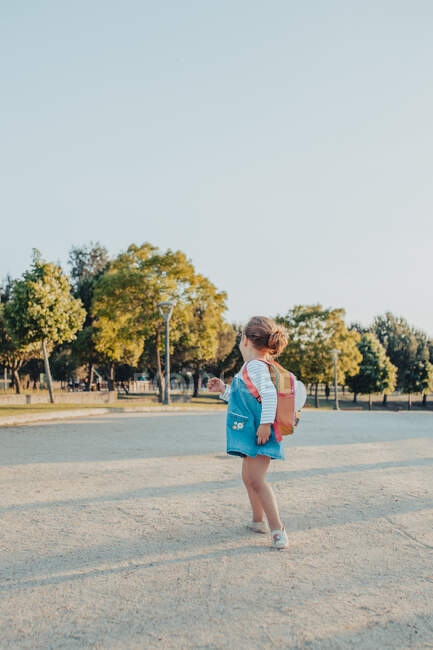 Side view cute little girl with backpack smiling and looking at camera while standing on sandy ground in park — Stock Photo