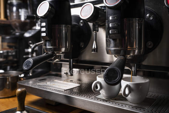 Professional coffee machine in restaurant dispensing freshly brewed espresso into two white cups — Stock Photo