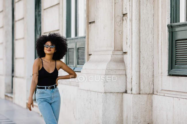Young ethnic woman in jeans and tank top walking and smiling at camera outdoors — Stock Photo