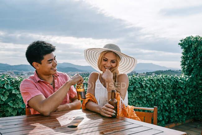 Una pareja bebiendo cerveza afuera y divirtiéndose - foto de stock