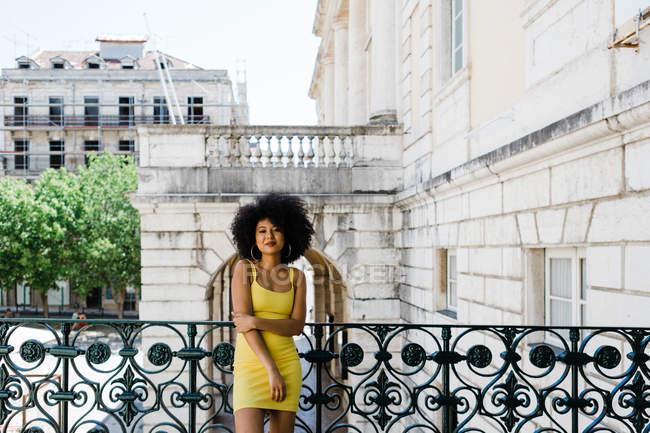 Donna afroamericana in abito giallo in piedi e guardando la fotocamera su sfondo urbano — Foto stock