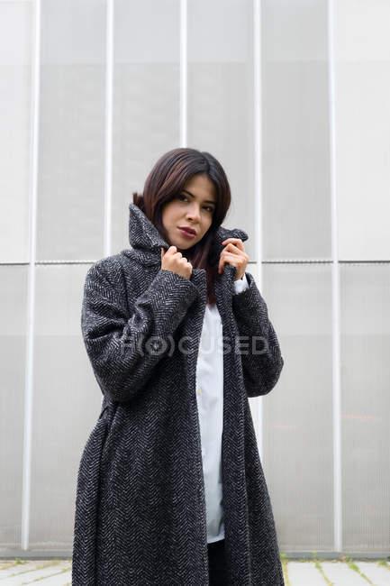 Jeune femme élégante regardant la caméra et enveloppant dans un élégant manteau chaud tout en se tenant debout sur la rue de la ville — Photo de stock