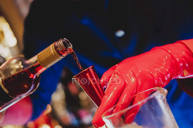 Невпізнаваний бармен у формі та червоних рукавицях готує коктейль і наливає напій червоній пляшці для змішування. — стокове фото