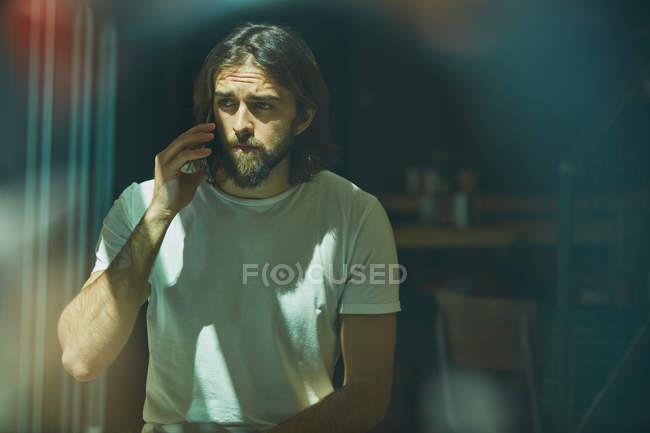 Giovane uomo bello barbuto in caffè dietro la finestra a parlare al telefono — Foto stock