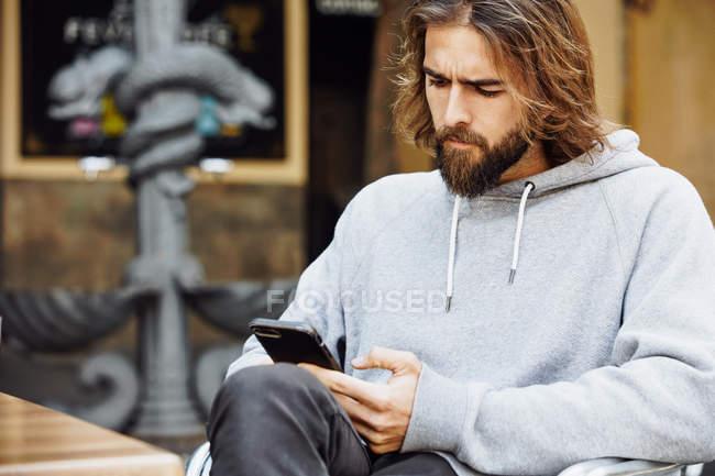 Joven hombre guapo barbudo en suéter casual sentado en la cafetería concentrado en el teléfono móvil - foto de stock
