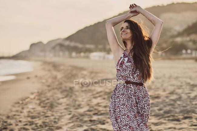 Bonne femme brune en robe d'été à la plage à l'heure d'or — Photo de stock