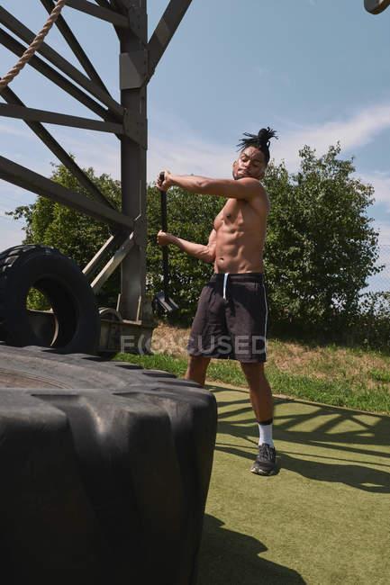 Мускулистый чернокожий парень забивает шины в спортивном зале — стоковое фото